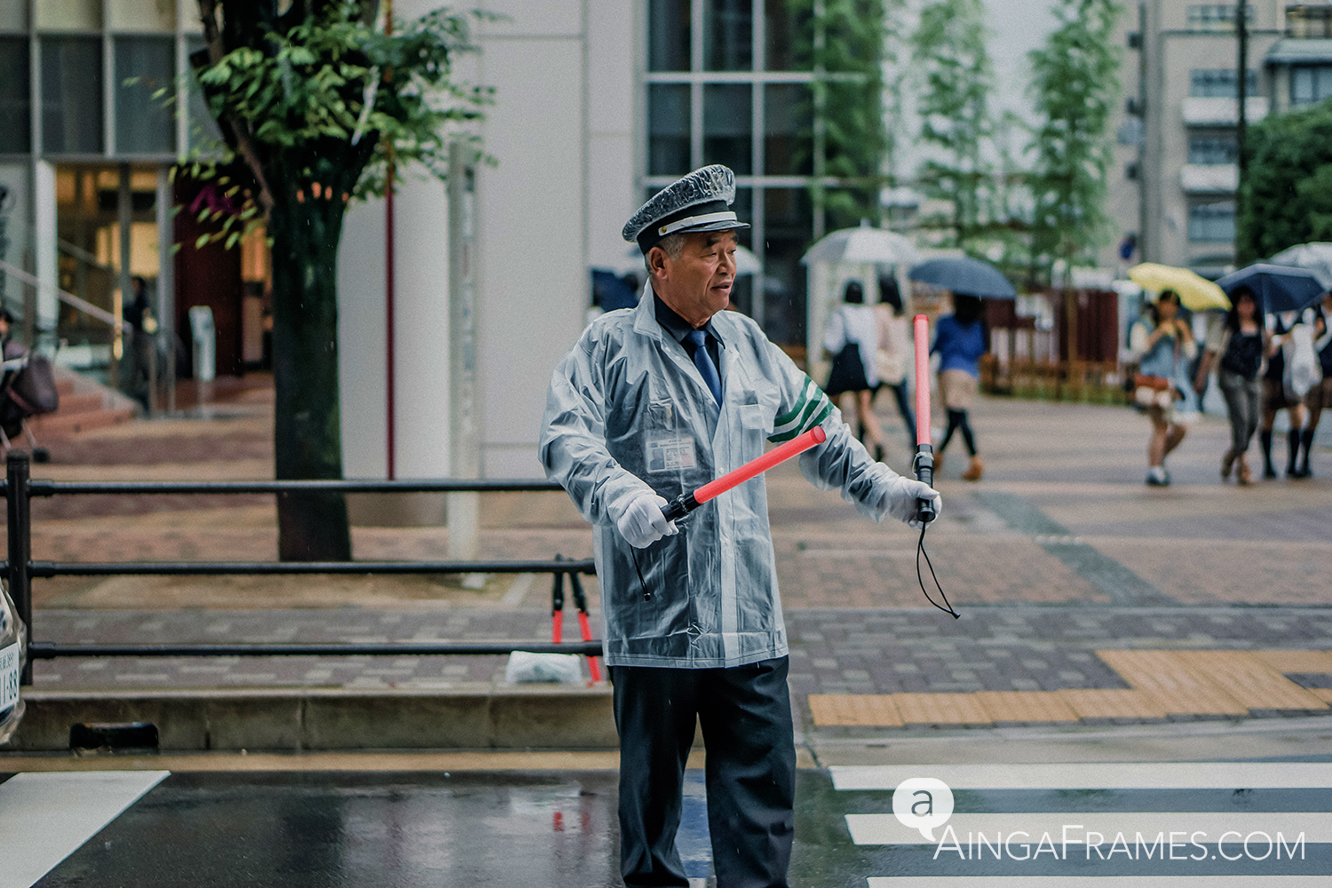 A crossing guard directing traffic in front of a giant shopping center in Kyoto on a cold, rainy day.