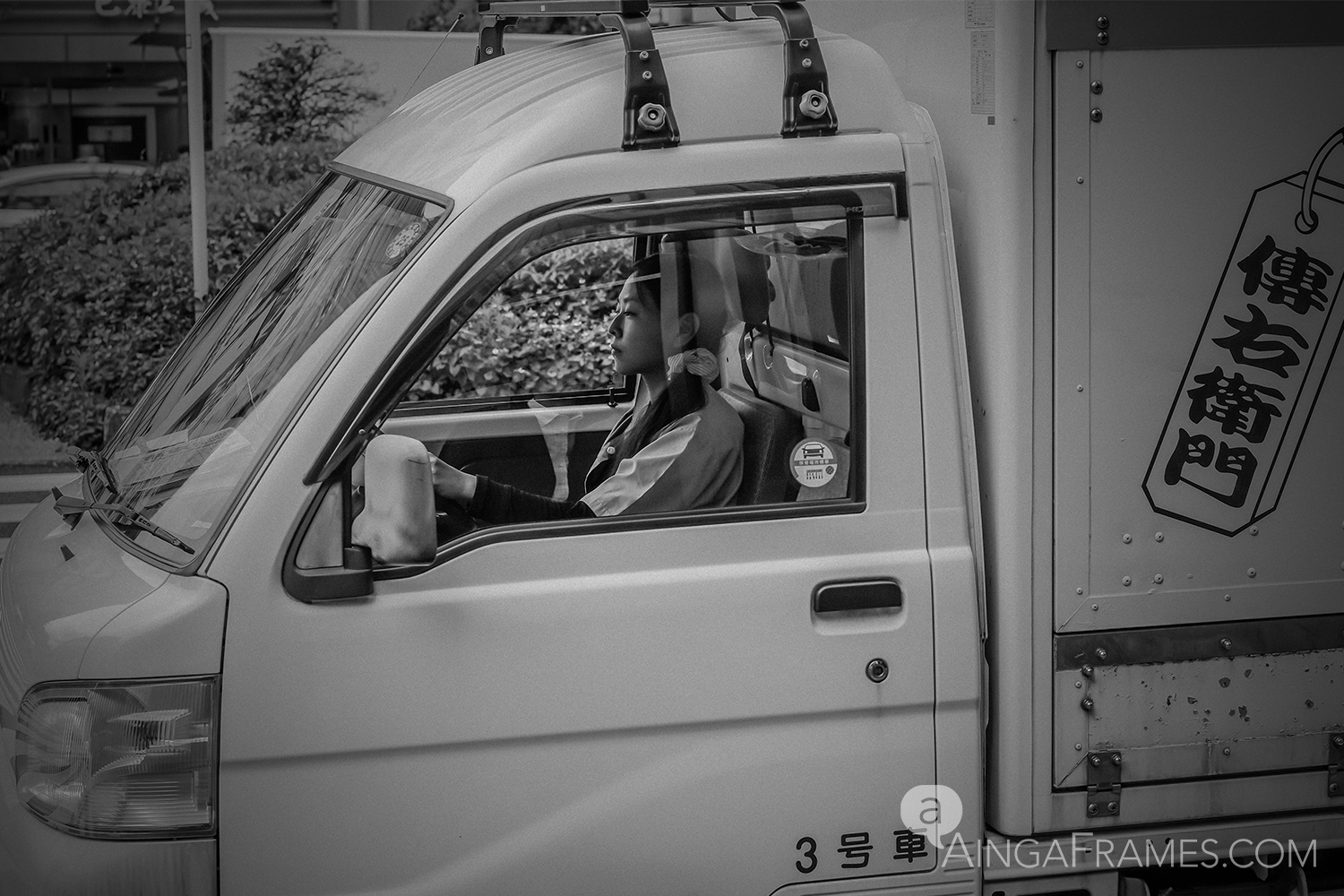 The expressionless face of the young female truck driver making her early morning run near Tsukiji, Tokyo.